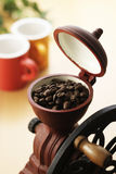 Coffee grinder. And cup on wooden table Royalty Free Stock Photos
