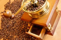 Coffee-grinder. With coffee beans on the wood desk Stock Photo