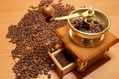 Coffee-grinder. With coffee beans on the wood desk Royalty Free Stock Photos