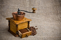 Coffee grinder. Old coffee grinder, coffee beans on cackcloth background, studio loghts Royalty Free Stock Image