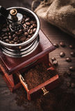Coffee grinder and beans. Antique coffee grinder with beans, dust and jute Royalty Free Stock Photos