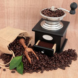 Coffee Grinder and Beans. Coffee grinder, beans and leaf sprigs over papyrus background Royalty Free Stock Photos