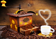 Coffee Grinder with Beans and coffe cup Royalty Free Stock Images