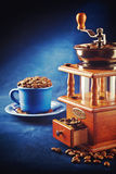 Coffee grinder with beans and cup on saucer standing on blue tab Stock Photography