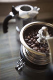 Coffee grinder with beans. A coffee grinder machine filled with coffee beans and a moka in background Royalty Free Stock Images