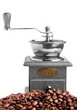 Coffee grinder and coffee beans around it Royalty Free Stock Photography