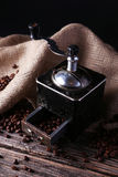 Coffee grinder with coffee beans on brown wooden background. Royalty Free Stock Image