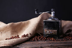 Coffee grinder with coffee beans on brown wooden background. Stock Photos