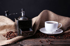 Coffee grinder with coffee beans on brown wooden background. Stock Photography