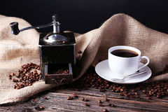 Coffee grinder with coffee beans on brown wooden background. Stock Photo