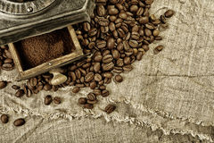 Coffee grinder and coffee beans on burlap fabric Royalty Free Stock Photography