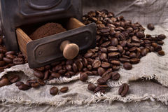 Coffee grinder and coffee beans on burlap fabric Royalty Free Stock Photo