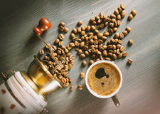 Coffee grinder, coffee beans and coffee cup on a wooden table Royalty Free Stock Image