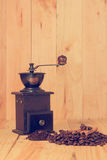 Coffee grinder and coffee beans. On wood table Stock Photography