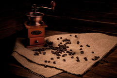 Coffee grinder and coffee beans. On a wooden background Stock Image