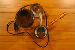 Coffee grinder and coffee boil container. On a wooden surface royalty free stock images