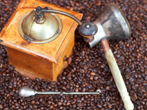 Coffee grinder and copper pot on roasted beans Stock Photos
