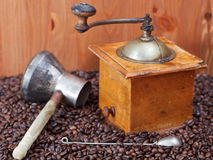 Coffee grinder and copper pot on roasted beans Royalty Free Stock Images