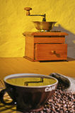 A coffee grinder and cup of coffee Royalty Free Stock Photos