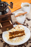 Coffee grinder, cup of coffee and cake Royalty Free Stock Photos