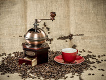 Coffee grinder an an cup of coffee on a jute bag Royalty Free Stock Image