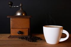 A coffee grinder and a cup of coffee. A picture of a coffee grinder and a cup of hot coffee on a wooden table Stock Image