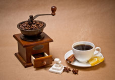 Coffee-grinder and cup of hot coffee. Coffee-grinder, cup of hot coffee, coffee beans, sugar, cinnamon sticks, two lemon slices and some star anise fruits  on Stock Images