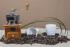Coffee grinder and cups on some bean Stock Image