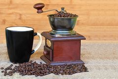 Coffee grinder full of roasted coffee beans and black mug Stock Image