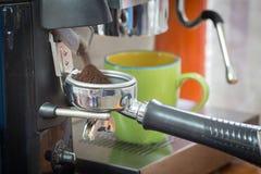 Coffee grinder grinding freshly roasted coffee beans Royalty Free Stock Images