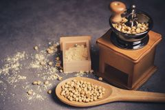 Coffee grinder grinding soybeans into powder and wooden ladle. Coffee grinder grinding soybeans into powder and wooden ladle in darkness. Used to make soy milk royalty free stock image