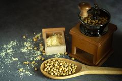 Coffee grinder grinding soybeans into powder and wooden ladle in darkness. Used to make soy milk royalty free stock images