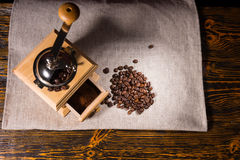 Coffee grinder, ground and beans on tablecloth Royalty Free Stock Image