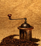 Coffee grinder and many beans. Old wooden coffee grinder and roasted ecological aromatic coffee beans, ready to make a good cop of taste and energy Royalty Free Stock Photos