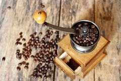 A coffee grinder. With roasted coffee beans on the old wood Royalty Free Stock Photography