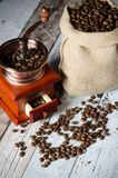 Coffee grinder with roasted beans. Vintage mill composition Royalty Free Stock Image