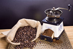 Coffee grinder and roasted coffee beans. Roasted coffee beans in a canvas bag and a coffee grinder Royalty Free Stock Images