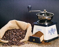 Coffee grinder and roasted coffee beans. Roasted coffee beans in a canvas bag and a coffee grinder Royalty Free Stock Photography