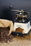 Coffee grinder and roasted coffee beans. Roasted coffee beans in a canvas bag and a coffee grinder Stock Image