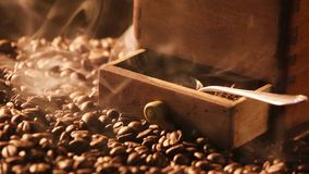 Coffee grinder standing on freshly roasted coffee beans stock video footage