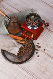 Coffee grinder, turk and cup of coffee on wooden background. Stock Photography