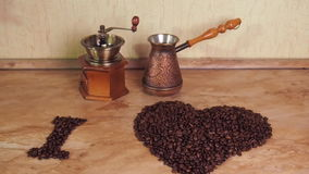 Coffee grinder and Turk on the kitchen table with coffee beans. Inscription from coffee beans. Heart of coffee beans. The inscript stock video footage