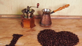 Coffee grinder and Turk on the kitchen table with coffee beans. Inscription from coffee beans. Heart of coffee beans. The inscript stock video