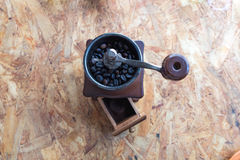 Coffee grinder on wood table. Coffee grinder with coffee bean on wood table royalty free stock image
