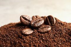 Coffee grounds and roasted beans on table. Closeup royalty free stock image
