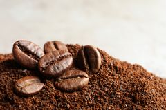 Coffee grounds and roasted beans on table. Closeup stock images