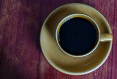 Coffee on grunge wood table. Close-up on cup of coffee with dark colored textured background royalty free stock image