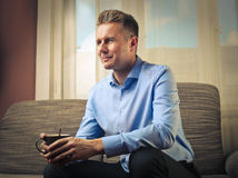 Coffee in hand. Man sitting on sofa holding cup stock photos