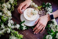 Coffee in hand and white flowers. stock images