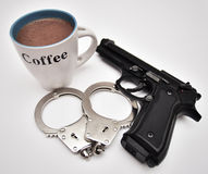 Coffee, handcuffs and hand gun Stock Photos